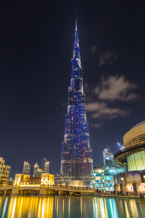 DUBAI, United Arab Emirates (UAE) - 18  February 2017. Illuminated tower Burj Khalifa against the dark sky with clouds at night. Reflection of lights in the water. Highest in the world skyscraper (828 m)