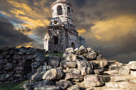 Old park Schwetzingen, Germany -  ruins of the temple of Mercury against a backdrop of dramatic sunset, clouds are illuminated by the sun