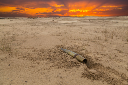 old artillery metal projectile on the sand in the desert against the background of dramatic sunset. concept of war Stock Photo