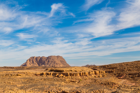 Sinai stone desert and single mountain on  bright day against the blue cloudy sky. Egypt landscape Stock Photo