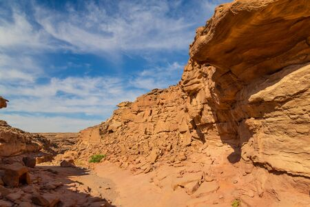 Colorful  canyon in Sinai desert, Egypt - old weathered rocks against the blue sky and white clouds. Tourist destination