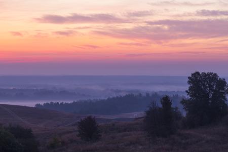 Morning autumn landscape: fog over hills and forest on background of red sunrise.  View from above. Village Opishnya, Poltava region, Ukraine