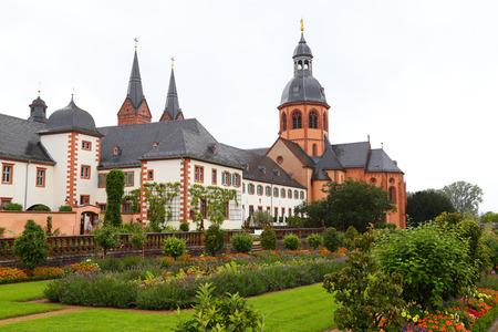 Ancient medieval monastery Seligenstadt : historic baroque building  Basilika Saint Marcellinus and Petrus (  Einhard-Basilika ), Benedictine abbey and multicolored vegetable garden and formal park. Germany. Popular tourist destination