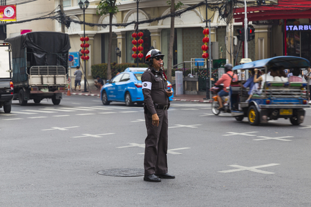 24.02.2018. Chinatown in Bangkok, Thailand . Yaowarat Road. The traffic policeman regulates the busy traffic on a city street. Famous tourist attraction, tourist attraction Banco de Imagens - 101460388