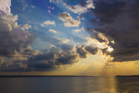Colorful sunset on the river Dnipro. Ukraine. The rays of the sun breaking through the dark clouds. Solar path on the water. Nature landscape