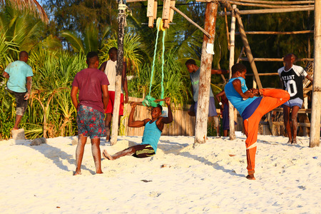 12.02.2019. Island Zanzibar, Tanzania. Africa. African young people, living in the village, doing sport exercises on handmade gym equipment. Workout on the sand Редакционное