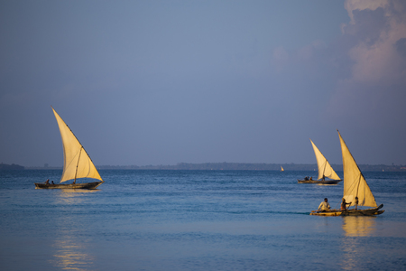 Ancient wooden sailing boats with people on board on the sea surface at the morning. Coast of  Zanzibar island , Tanzania, Africa. Preservation of national traditions, ancient crafts, historical lifestyle
