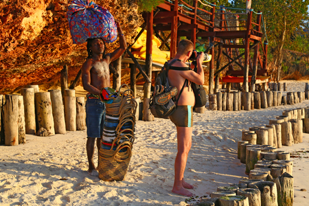 02.12.2019 Ocean coast of Zanzibar island. Tanzania. Africa. Young african man is a basket seller and a European man is a photographer. Local people and tourists. Tourist destination 新聞圖片