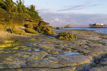 Morning on the ocean coast at low tide. Coastal rocks, wooden pedestrian bridge leading into the water. Zanzibar coast, Nungwi village. Tourism destination
