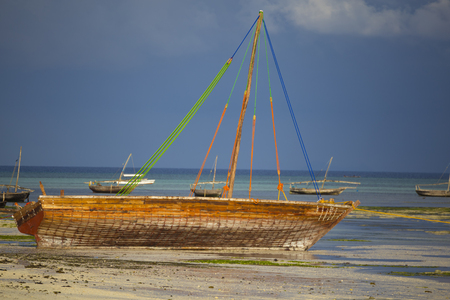 National traditional wooden african boat, closeup, in shallow water. Boats on the ocean surface. Coast of island Zanzibar. Tanzania
