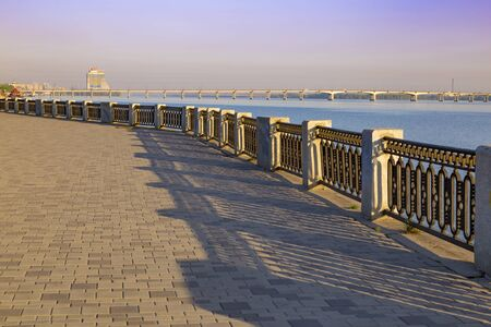 Pedestrian embankment along river Dnipro and bridge at spring bright day. Dnipro city, city view. Ukraine.