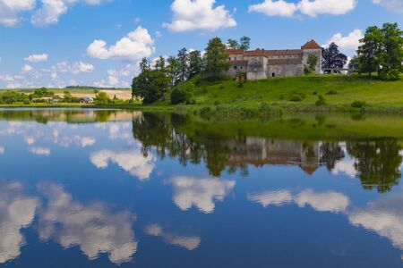Castle on the lake. Beautiful scene with ancient Svirzh ( Svirz ) castle on the hill against the blue sky and white clouds, surrounded by lake. Lviv region.  Ukraine. Tourist destination, landmark