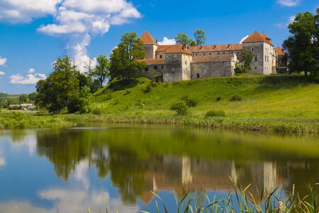 Beautiful scene with ancient Svirzh ( Svirz ) castle on the hill against the blue sky and white clouds, surrounded by lake. Lviv region.  Ukraine. Tourist destination, landmark Banco de Imagens