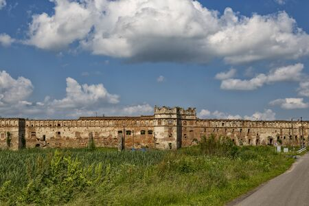 Citadel. Ancient ruins of Stare Selo castle outside, brick wall  with loophole against the blue cloudy sky. Fortress in Stare Selo, Lviv region. Ukraine. Tourist destination, landmark Banco de Imagens
