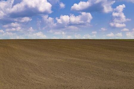 Landscape with agricultural land, arable land, recently plowed and prepared for the crop, on blue cloudy background. Ukraine