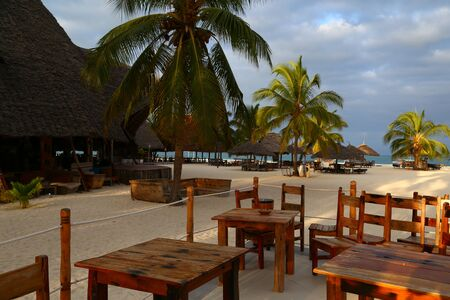 Morning on the ocean coast. Umbrellas and palm trees on the beach. Ocean shore of Zanzibar island. Holiday paradise. Village Kendwa, Tanzania, Africa. Tourist destination, beach holiday, relaxation