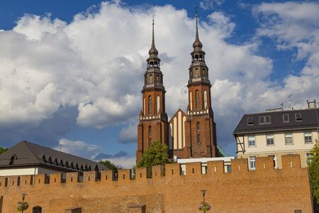 Opole city, southern Poland  is one of the oldest cities in Poland.View on the fortress wall and Cathedral Basilica of the Holy Cross on blue cloudy sky background. Tourism destination, tourist landmark Banco de Imagens