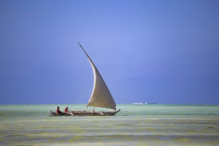 Authentic wooden sailing boat with african people on board on the sea surface on blue sky background. Coast of  Zanzibar island , Tanzania, Africa. Preservation of national traditions,  historical lifestyle