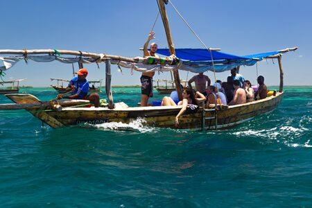 02.16.2019 Island Zanzibar, Tanzania. Africa.Tourists  travel on  wooden national boat, accompanied by African guides against the background of the turquoise ocean and blue cloudy sky. Sea tour for tourists. Tourism destination, adventure, beach vacation.