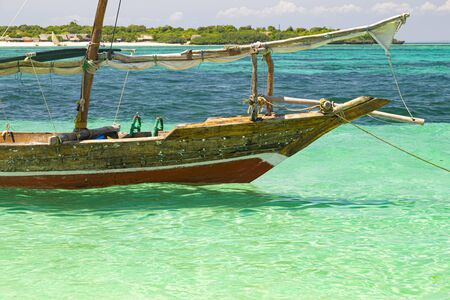 Ancient wooden african boat, close-up. Boat on the waves of azure ocean surface on blue bright background. Coast of island Zanzibar, Africa Standard-Bild