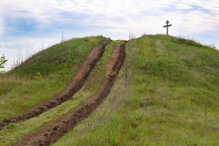 Dirt road going to the top of  green hill against  blue cloudy sky. Cross on top.  Surroundings of Opishnya village, Poltava region, Ukraine Standard-Bild