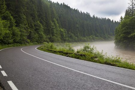 Mountain landscape: stormy mountain river Prut and asphalt road in the Carpathian mountains. Ukraine