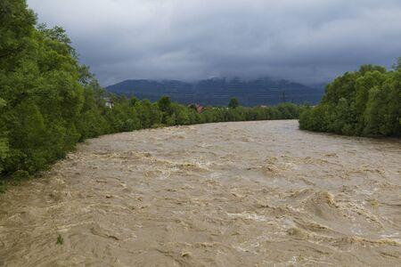 Wide stormy mountain river among green mountains after rain. Location: Prut River, Yaremche village, Carpathians, Ukraine. Standard-Bild