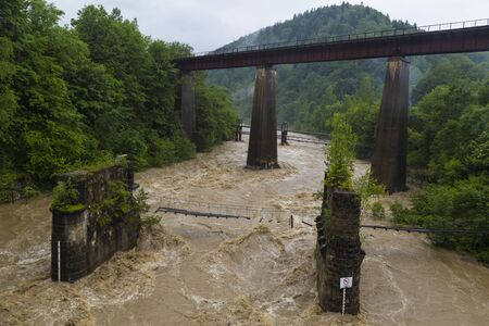 Picturesque railway bridge and a destroyed bridge over a stormy mountain river among green mountains. Location: Prut River, Yaremche village, Carpathians, Ukraine.