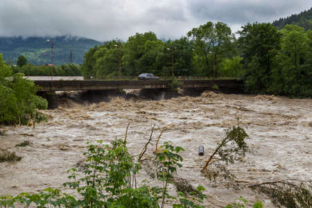 Wide fast stormy mountain river Prut flows under the bridge. Natural disasters in the Carpathians village, Carpathian mountain. Ukraine Standard-Bild
