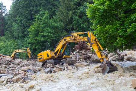 Yaremche village, Carpathian region, Ukraine. Catastrophic flood that caused the collapse of the mountain, blockage and destruction of the road. Power shovel work