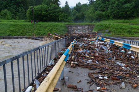Bridge over mountain river Prut with dirt and rubbish afteк flood. Carpathians. Ukraine. Ecological disaster, environmental pollution by human waste products