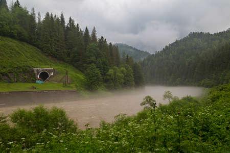 Wide fast mountain Prut river flowing among green hills and railway tunnel in fog. Yaremche village, Carpathian mountain. Ukraine