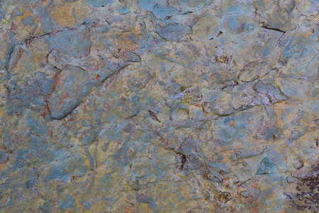 Gray, blue and brown colored textured natural stone surface of rock. Stone pattern abstract background. Rock structure outdoor. Standard-Bild
