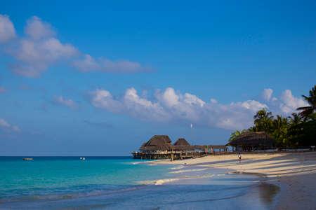 Beach resort at the morning. Palm trees, sand, turquoise ocean against the blue cloudy sky. Ocean coast of Zanzibar island. Village Kendwa. Tanzania. Africa. Tourist destination, beach holiday. Standard-Bild