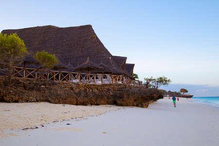 Beach resort at the morning. Vacationers, tourists walking along the ocean coast. Zanzibar island. Village Nungwi. Tanzania. Africa. Tourist destination, beach holiday, ssummer vacation. Standard-Bild