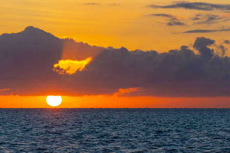 Dramatic sunset over ocean coast. The setting sun on the horizon. Dark clouds on red sky background. Location: Nungwi Beach. Island Zanzibar, Tanzania, Africa.
