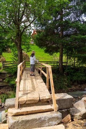 Woman - hiker on wooden pedestrian bridge through a mountain river. Summer holidays in the Carpathian mountains. Ukraine. Tourism, active lifestyle