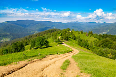 Mountain summer landscape. Trail among the forest against the background of mountain peaks and sky. View from Makovytsia mountain, Yaremche area. Carpathians. Ukraine. Standard-Bild