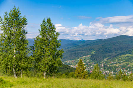 Mountain summer landscape. Forest against the background of mountain peaks and sky. View from Makovytsia mountain, Yaremche area. Carpathians. Ukraine.