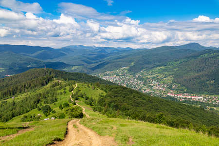 Mountain summer landscape. Trail among the forest against the background of mountain peaks and sky. View from Makovytsia mountain, Yaremche area. Carpathians. Ukraine.