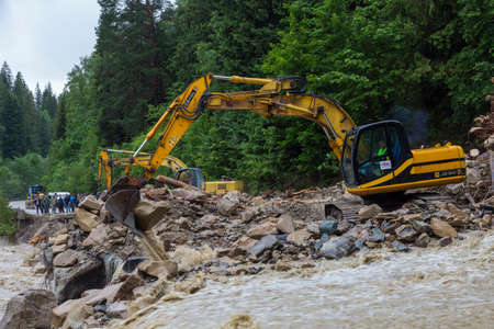 07.23.2020 Yaremche village, Carpathian region, Ukraine. Catastrophic flood that caused the collapse of the mountain, blockage and destruction of the road. Excavator work
