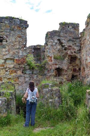Female tourist on ruins on medieval abandoned Pniv castle. Nadvirna city, Ivano-Frankivsk region, western Ukraine. Ruined fortress. Tourism, travel