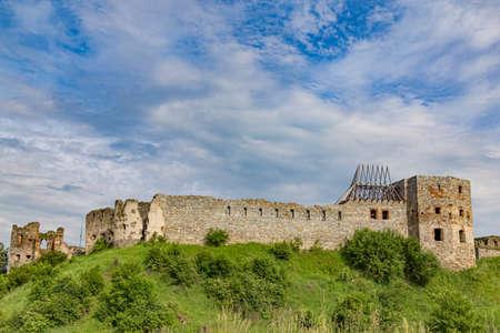 Scenic view on medieval abandoned Pniv castle, Nadvirna city, Ivano-Frankivsk region, western Ukraine. Fortress on green hill on sky background. Standard-Bild