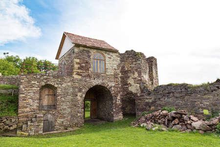 Scenic ruins of medieval castle Pidzamochok among the green grass, Buchach region, Ternopil Oblast, Ukraine. Tourist landmark, tourist destination.