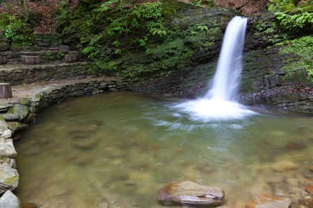 Nature landscape with the cascade stream of the forest mountain river. Waterfall Krutylo on Turichka river near Lumshory village of TransCarpathia, Carpathians. Ukraine.