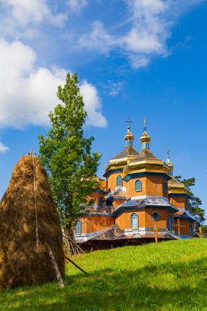 Beautiful ancient wooden Saint Nicholas church in Koziova villade on picturesque green hill and blue sky background. Carpathian Beskids, Skole Beskids National Park.