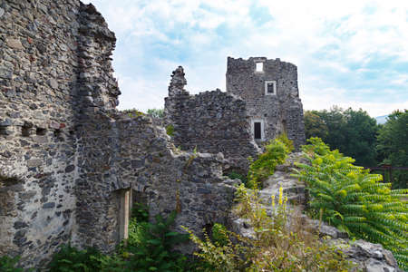 Scenic ruins of medieval Nevytsky (Nevytske) castle inside, overgrown with grass. Transcarpathian region. Ukraine. Tourism destination, tourist landmark.