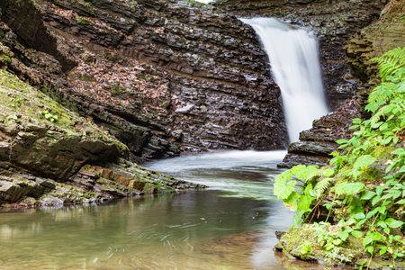 Nature landscape with the cascade stream of the forest river. Waterfall Krutylo on Turichka river near Lumshory village of TransCarpathia, Carpathians. Ukraine.