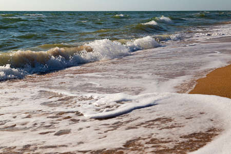 Sea coast. Seascape with stormy waves, yellow sand against the sky. Waves rolling on the sandy shore. Sea of Azov. Ukraine Standard-Bild