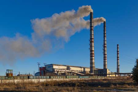 Coal-fired power station. Burshtyn city. Western Ukraine. Smoke stacks at coal burning power plant on blue sky background. Environmental pollution Standard-Bild